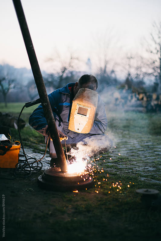Welder welding in the backyard during sunset by Marija Mandic for Stocksy United