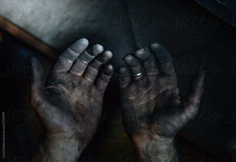 Man's hands covered in black soot by Cara Dolan for Stocksy United