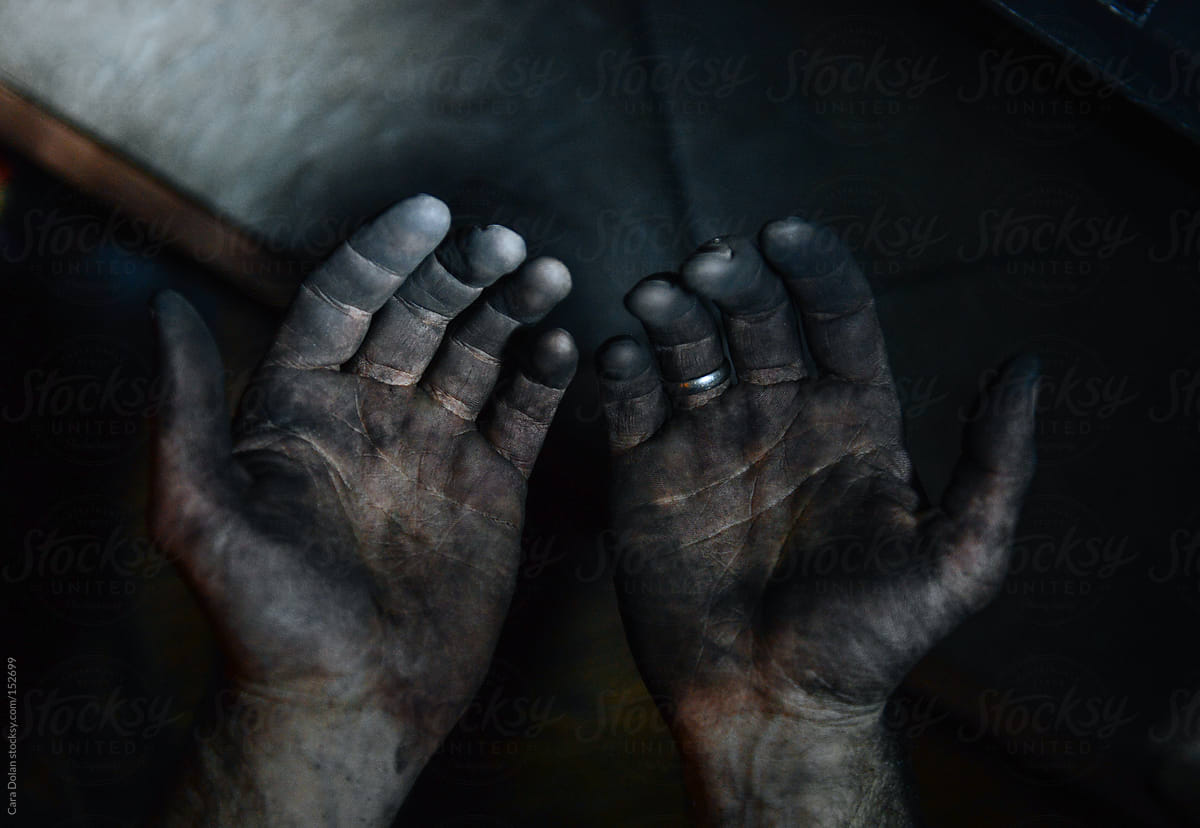 Man's hands covered in black soot by Cara Dolan - Stocksy United