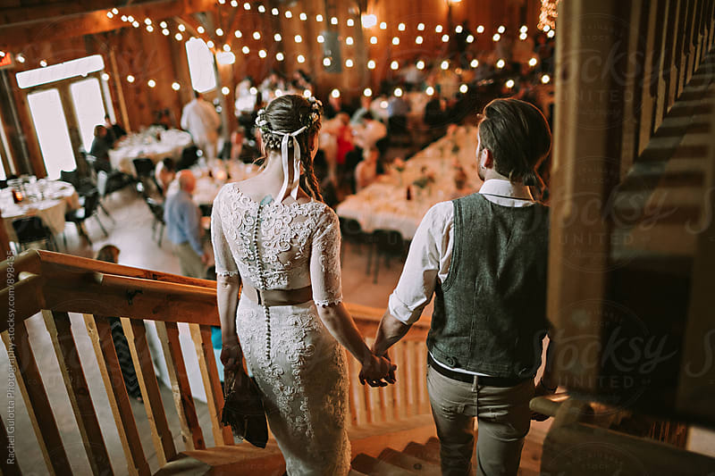 Bride and Groom Walking and Holding Hands by Rachel Gulotta Photography for Stocksy United