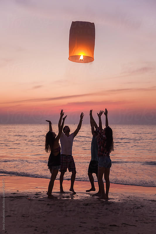 Friends releasing a lantern at the beach in Thailand by Jovo Jovanovic for Stocksy United