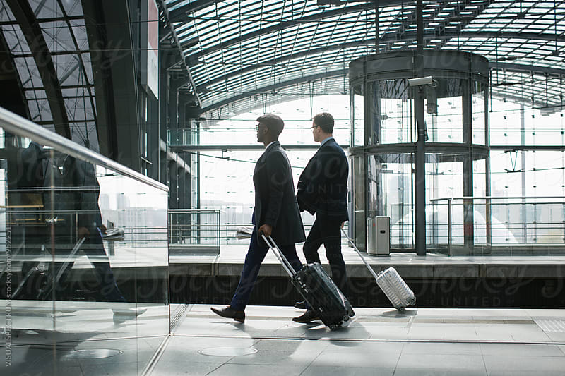 Two Business Travelers Walking With Carry On Suitcases in Modern Train Station by Julien L. Balmer for Stocksy United