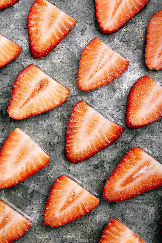 Sliced strawberries by James Ross for Stocksy United