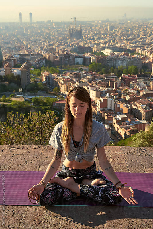 Tattooed woman relaxing in yogic position in morning by Guille Faingold for Stocksy United