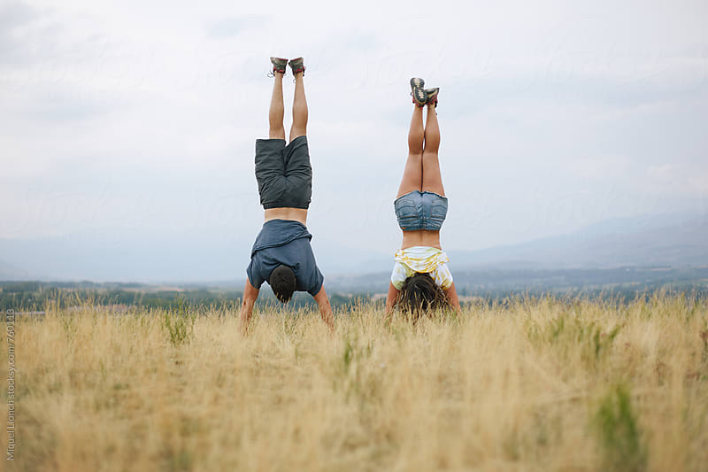 Handstand by two young people outdoors by Miquel Llonch for Stocksy United