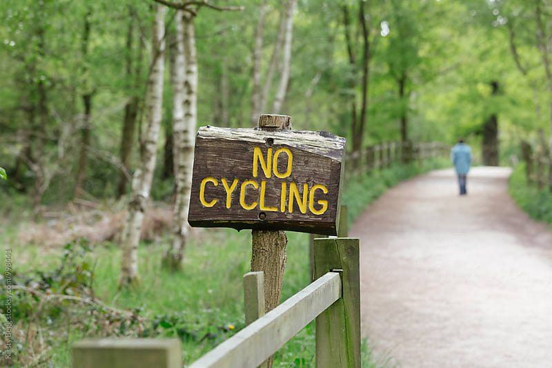 No cycling sign on trail with anonymous person walking in distance by Kirsty Begg for Stocksy United