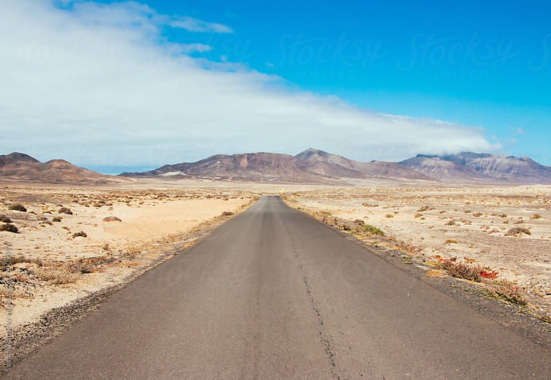 Landscape straight road towards some mountains by Susana Ramírez for Stocksy United