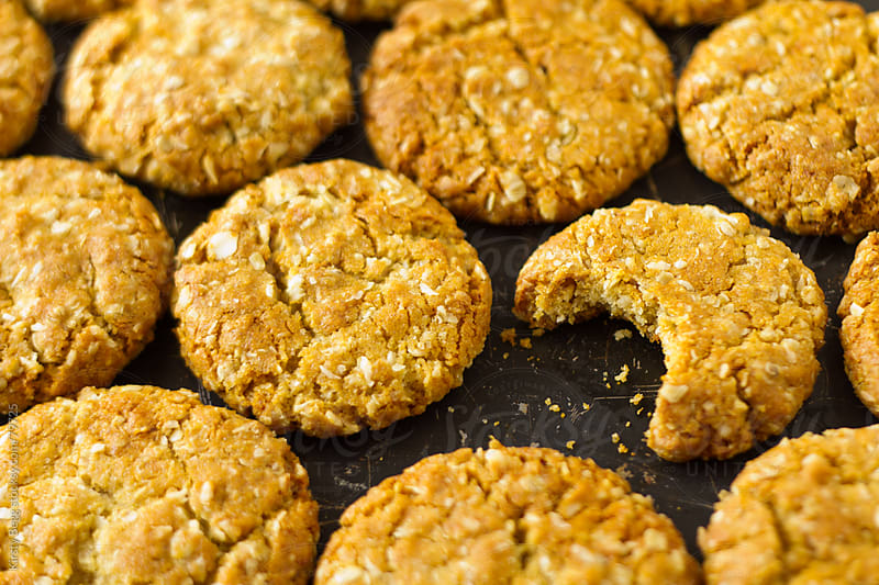 ANZAC biscuits oat cookies one bitten by Kirsty Begg for Stocksy United
