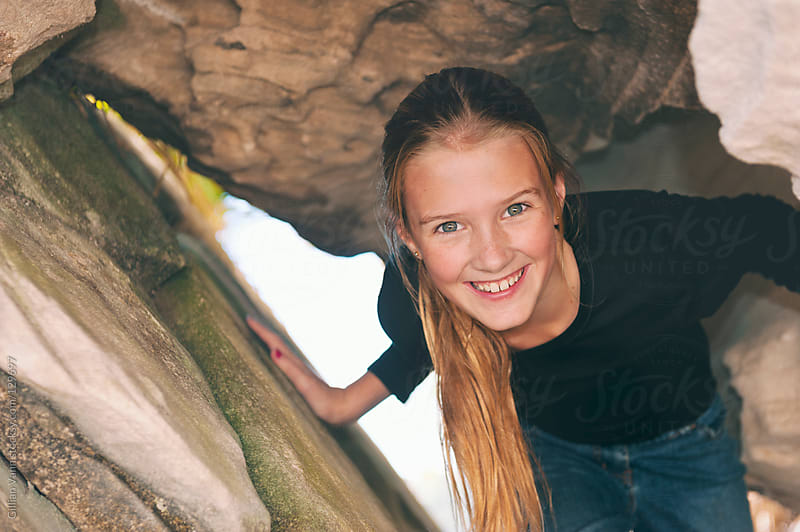 tween playing in the rocks at the beach by Gillian Vann for Stocksy United