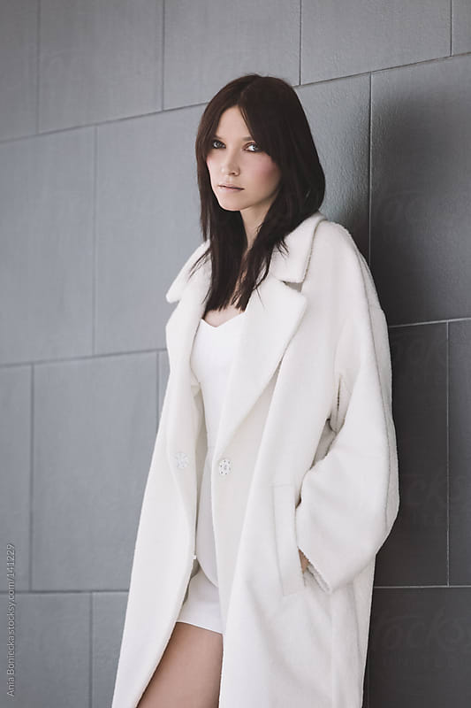 A portrait of a beautiful woman in a white winter coat by Ania Boniecka for Stocksy United