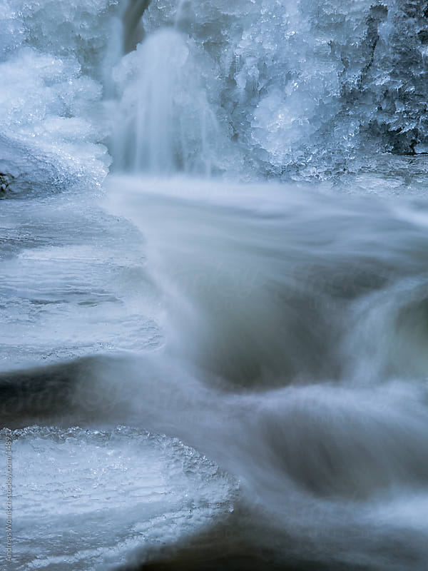 Closeup of the Flow of a small Stream between Ice and Snow by Andreas Wonisch for Stocksy United