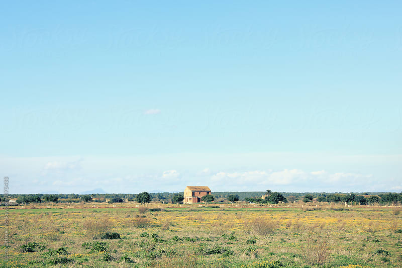 Mallorca landscape with a rural house in the distance by Lucas Ottone for Stocksy United