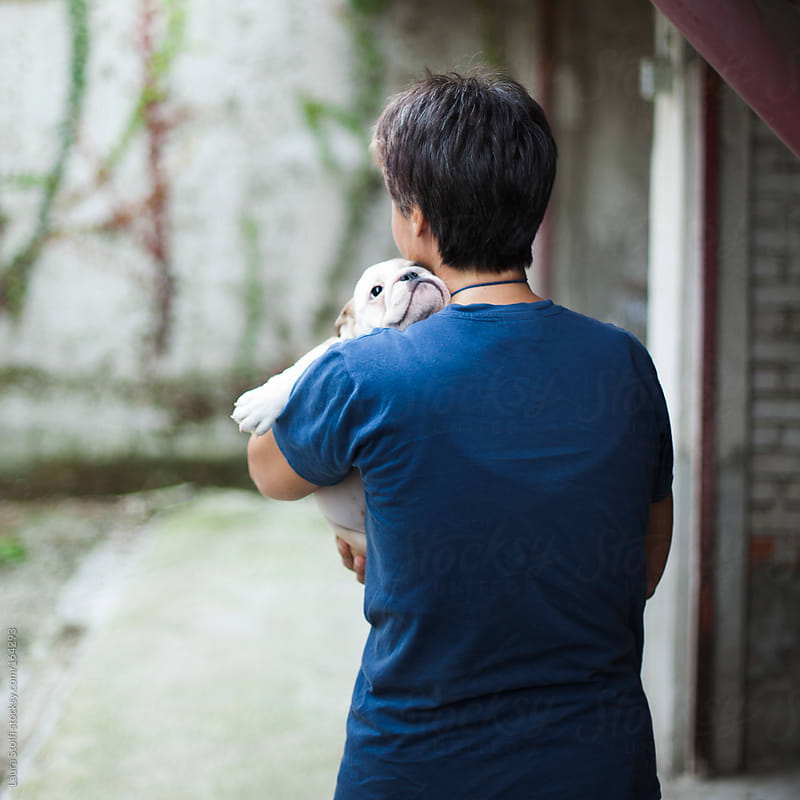 Rear sight of woman hugging bulldog puppy by Laura Stolfi for Stocksy United