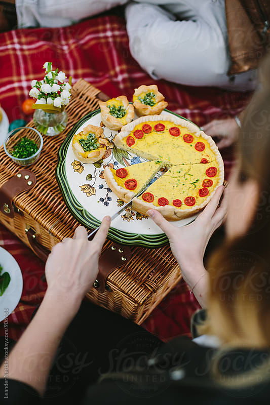 group of friends sharing a vegetable quiche outdoors on red picnic blanket by Leander Nardin for Stocksy United