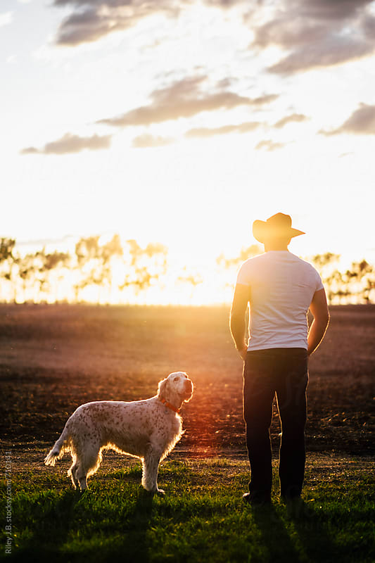 Cowboy standing in field at sunset with his dog by Riley Joseph for Stocksy United