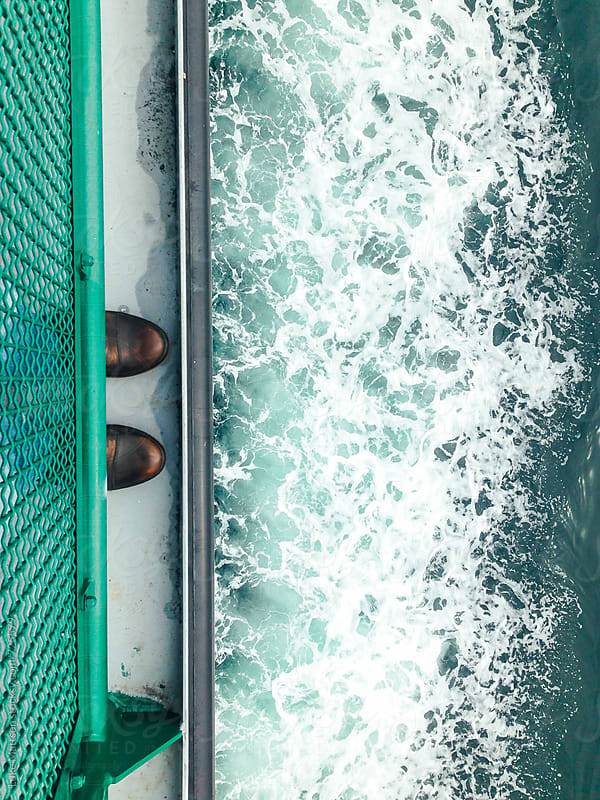 Boots Of A Passenger Poking Out From Under A Ferry Rail Above The Sea by Luke Mattson for Stocksy United