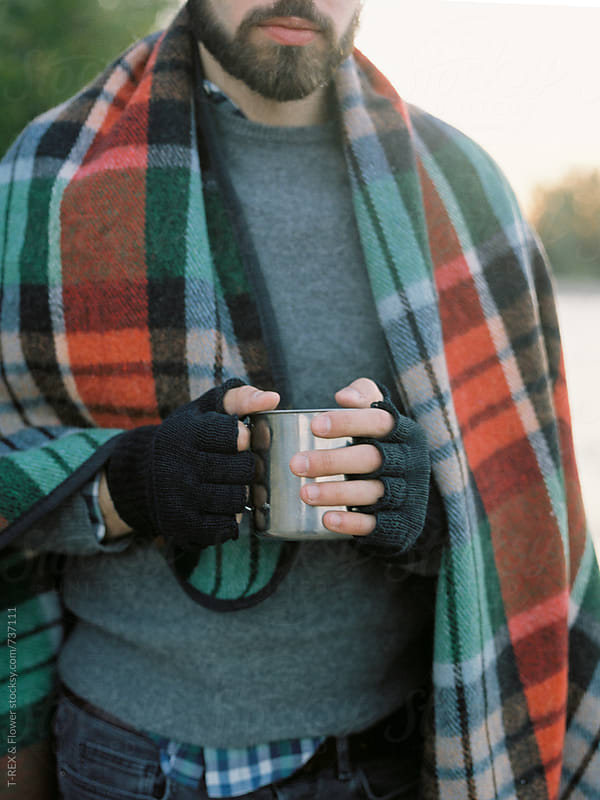 Man standing wrapped holding hot cup of tea by Danil Nevsky for Stocksy United