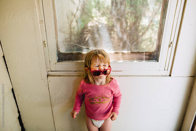 Small child making a funny face in sunglasses by Jessica Byrum for Stocksy United