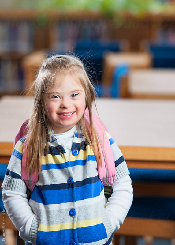 Smiling Girl Student with Down Syndrome in School Library by Brian McEntire for Stocksy United