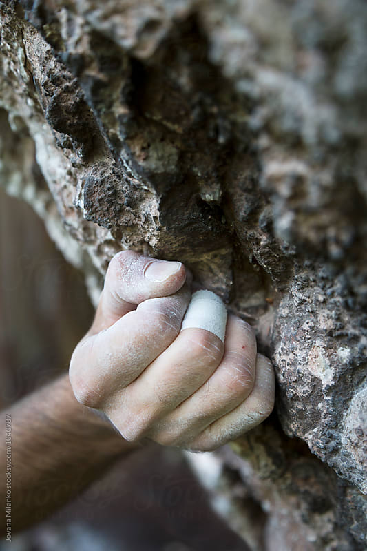 Hand of a free climber holding a rock hold on a natural wall by Jovana Milanko for Stocksy United
