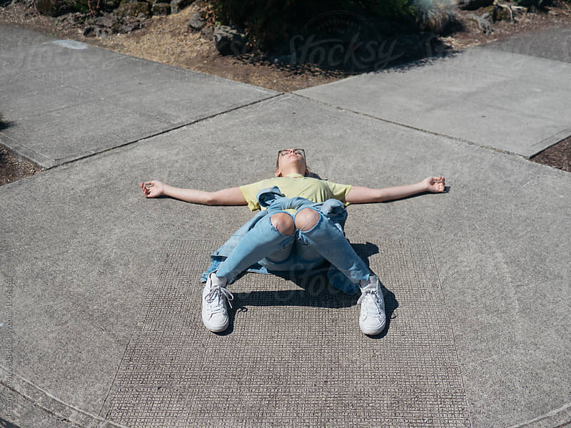 Exhausted young woman laying on summer sidewalk by Jeremy Pawlowski for Stocksy United