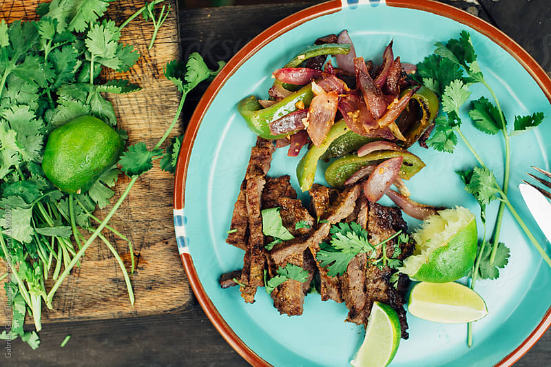 Grilled beef fajitas on a plate by Gabriel (Gabi) Bucataru for Stocksy United