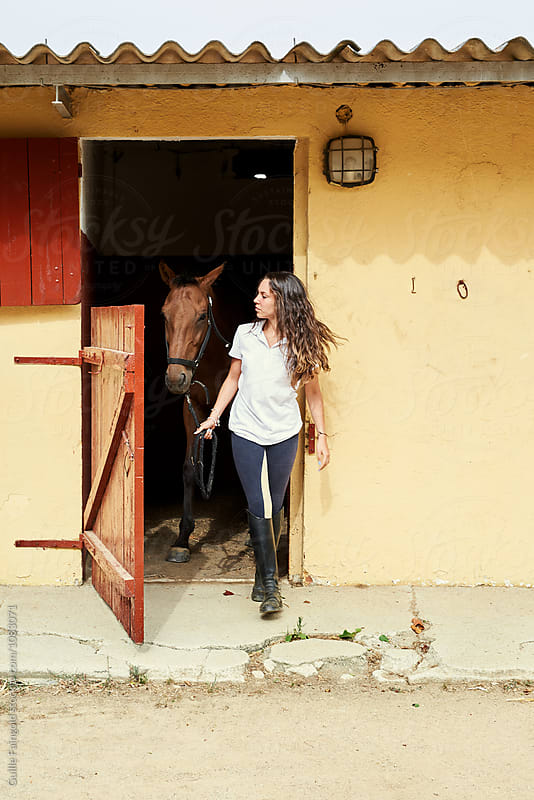 Teen girl leading horse out of stable by Guille Faingold for Stocksy United