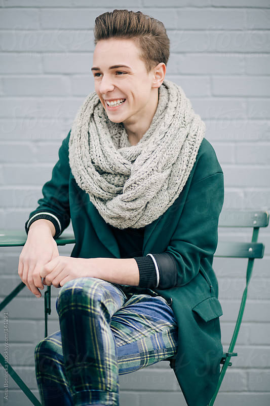 A stylish young man sitting at an outdoor patio laughing by Ania Boniecka for Stocksy United