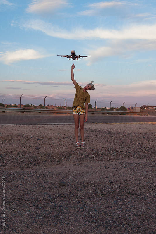 Girl pointing up at airplane by Image Supply Co for Stocksy United