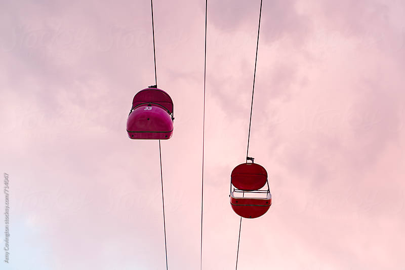 Empty amusement park ride with a pink sky background by Amy Covington for Stocksy United