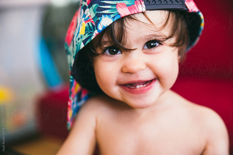 Stylish baby wearing a colourful flower cap smiling by Inuk Studio for Stocksy United