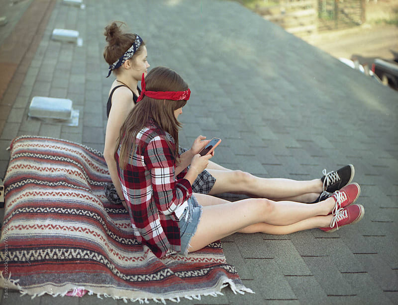 teenagers sit on rooftop of house by Tana Teel for Stocksy United