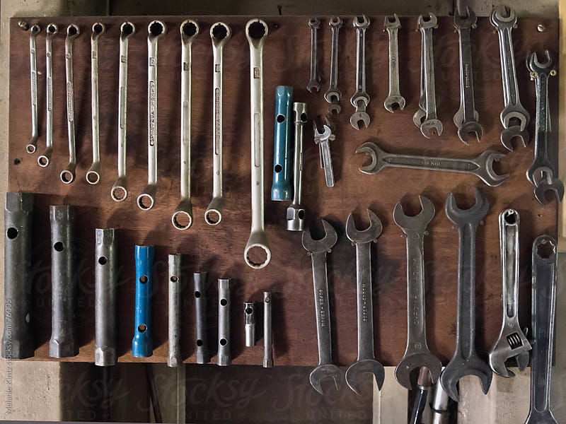 different sized wrenches sorted on a board in a workshop by Melanie Kintz for Stocksy United