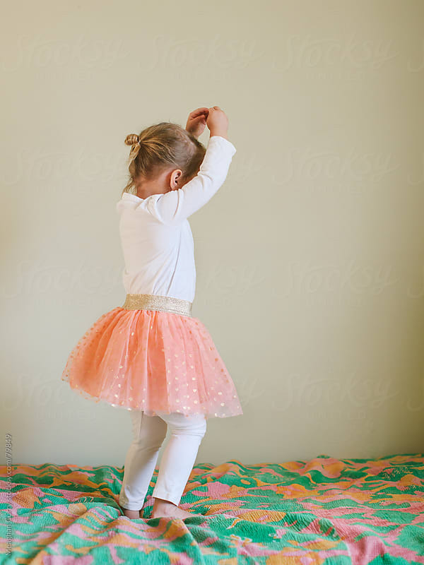 little ballerina on a bed by Meaghan Curry for Stocksy United