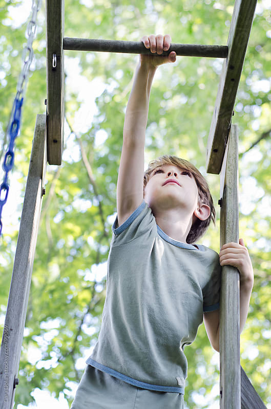 Child reaches high to reach the monkey bars of his backyard playset by Cara Dolan for Stocksy United