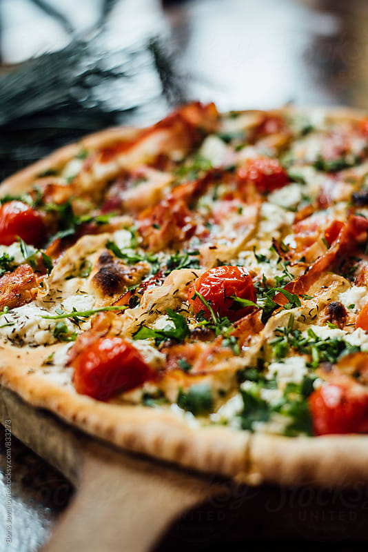 Close up of pizza with cherry tomato and bacon by Boris Jovanovic for Stocksy United