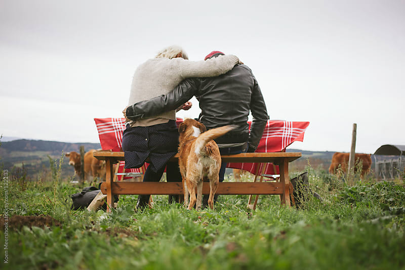 Embraced couple sitting at a picnic table with a dog in between them by Koen Meershoek for Stocksy United