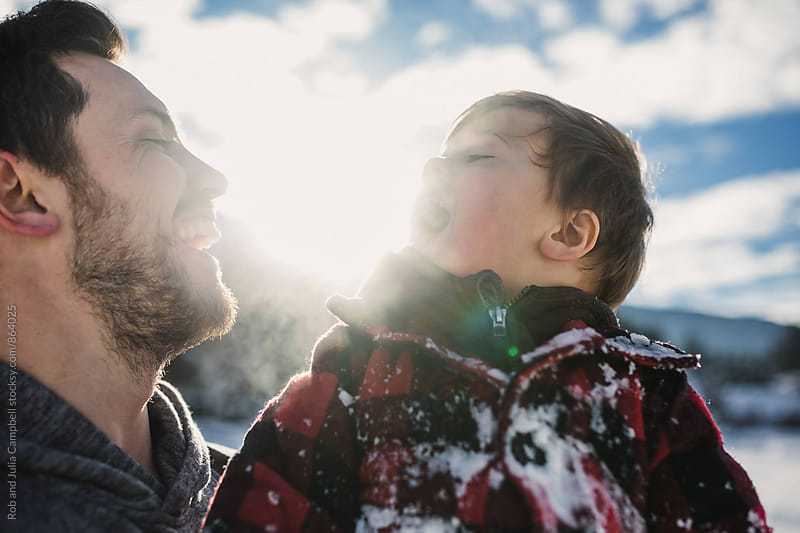 Loving young dad playing with son on frozen lake in winter by Rob and Julia Campbell for Stocksy United