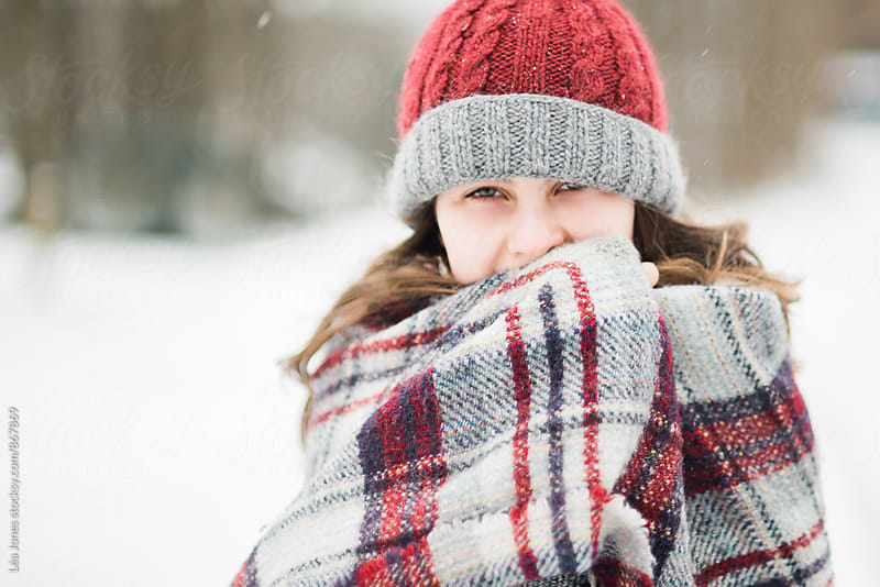 young woman wrapped in blanket in the snow by Léa Jones for Stocksy United