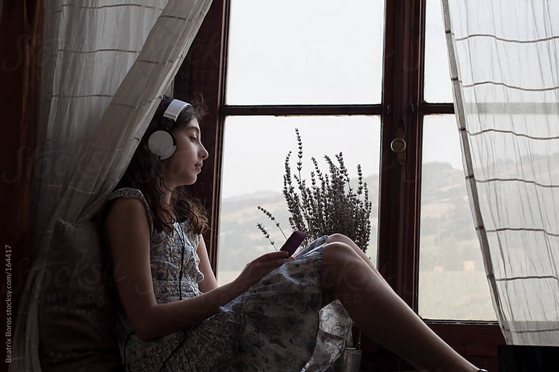 Girl listening to music with headphones at the window while watching Tuscan landscape by Beatrix Boros for Stocksy United