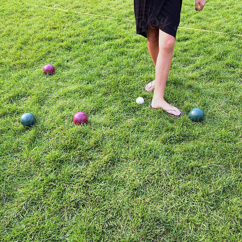 A Woman's Feet Measuring The Distance Between Bocce Balls During A Game by ALICIA BOCK for Stocksy United