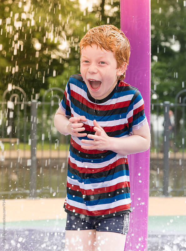 Child in a park playing in the water play area by Craig Holmes for Stocksy United