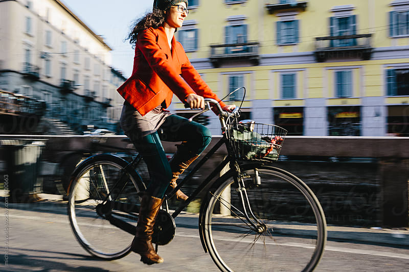 Young woman on a bicycle along the canals of Milan. by michela ravasio for Stocksy United