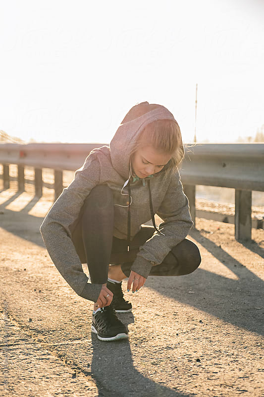 Blonde sportswoman tying up laces on road by Danil Nevsky for Stocksy United