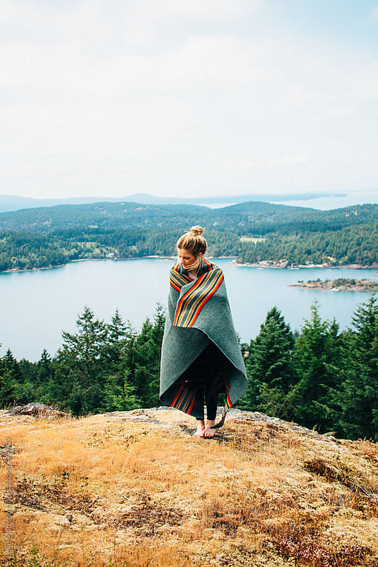 Young Blonde Woman Wrapped In Wool Blanket Standing On Forest Island Hillside by Luke Mattson for Stocksy United