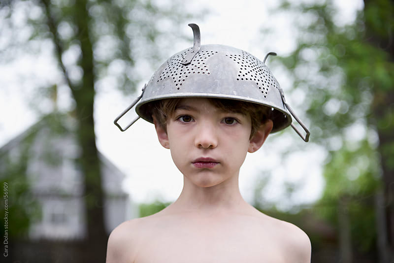 Tired boy wears colander as a hat by Cara Dolan for Stocksy United