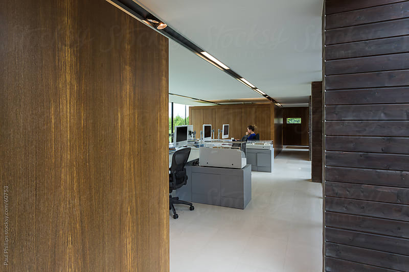 Solitary worker in an empty modern office by Paul Phillips for Stocksy United