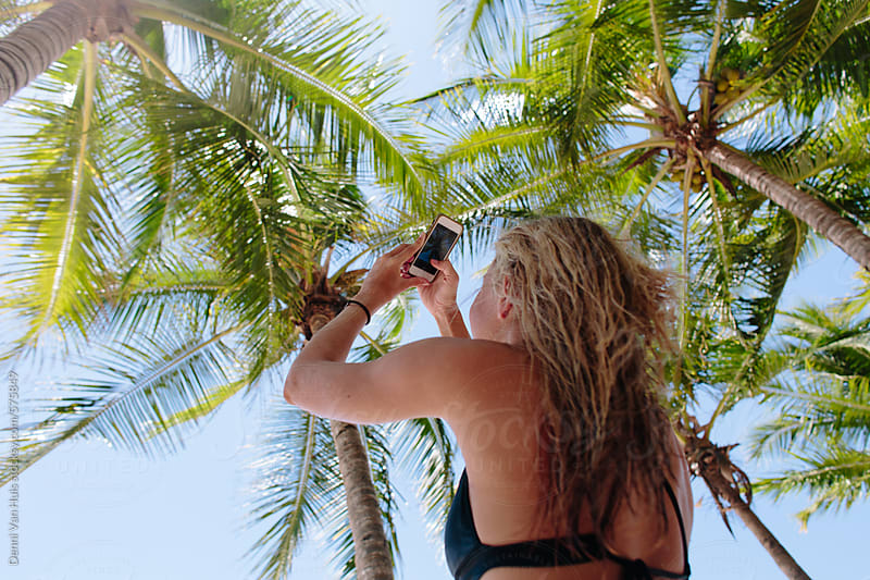 Woman taking a photo under the palmtrees with her phone. by Denni Van Huis for Stocksy United