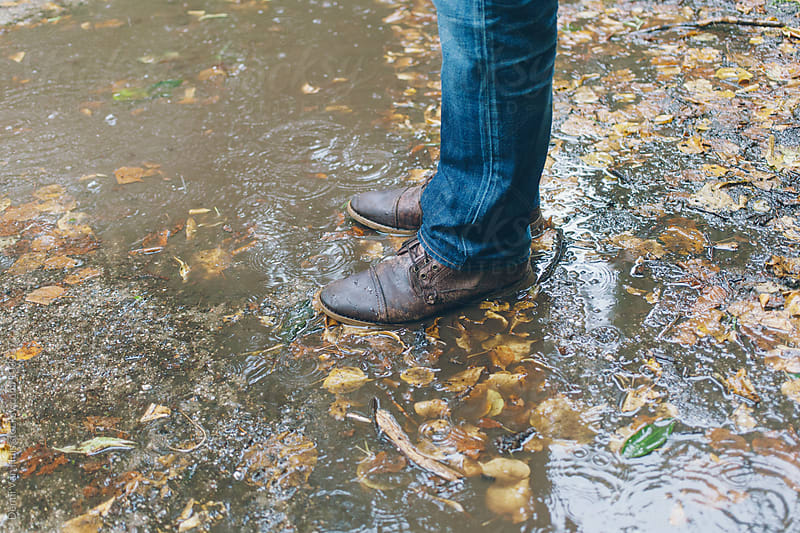 leather boots in a Brown Puddle of rainwater by Denni Van Huis for Stocksy United