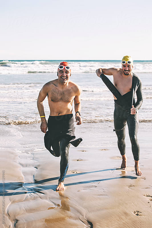 Two happy triathletes undressing wetsuit. by BONNINSTUDIO for Stocksy United